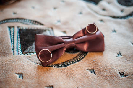 Pair of gold wedding rings on the red tiebow