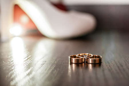 Three gold wedding rings and white high heel shoe on the table