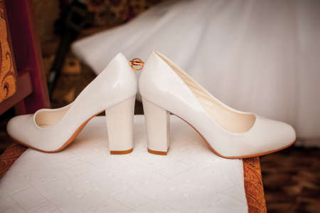 Pair of golden wedding rings between pair of a white shoes