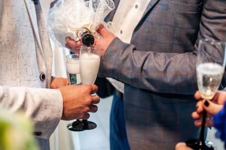 Man pours champagne into a glass