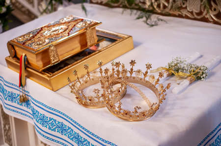 Bible golden crowns and pair of candles on the table