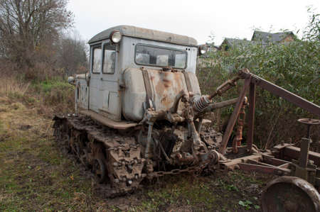 Old abandoned grey tractor near the field