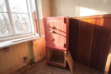 Red steel safe in the abandoned room