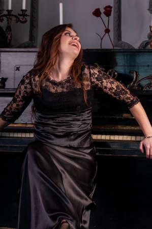 Woman laughs sitting at the piano Archivio Fotografico