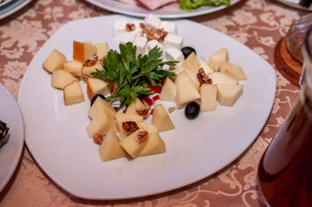 Wedding buffet. Slicing different varieties of cheese
