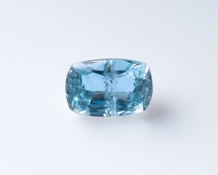 Natural faceted blue aquamarine on the white background