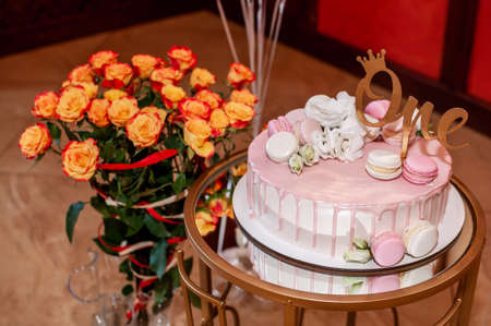 Festive cake on a stand and a bouquet of orange roses