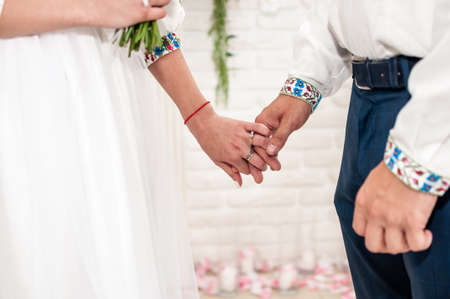 the groom holds the bride's hand at the ceremony in the registry office