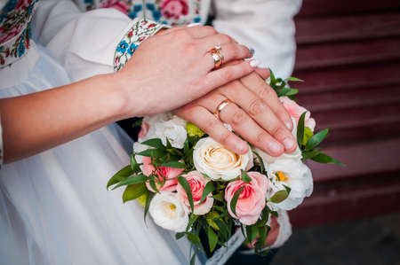 hands of newlyweds with wedding rings on a wedding bouquet with white and pink roses