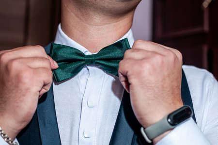 the groom straightens the green bow tie around his neck Banco de Imagens