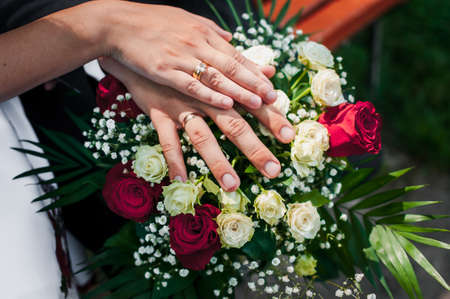 Wedding rings on the hands of the newlyweds at a wedding bouquet