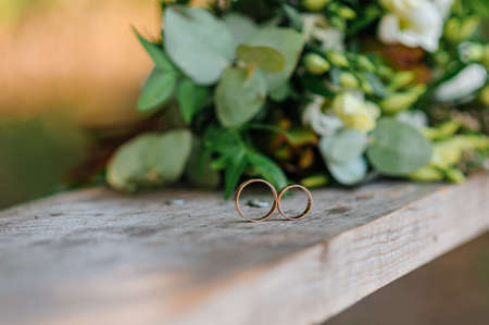 Wedding rings on a wooden stand against the background of the bride's bouquet