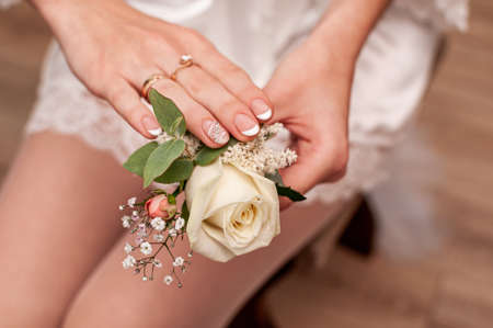 Boutonniere of the groom with white flowers in the hands of the bride