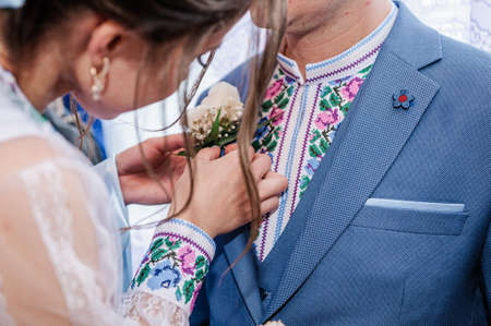 Boutonniere of the groom with white flowers in the hands of the bride Standard-Bild