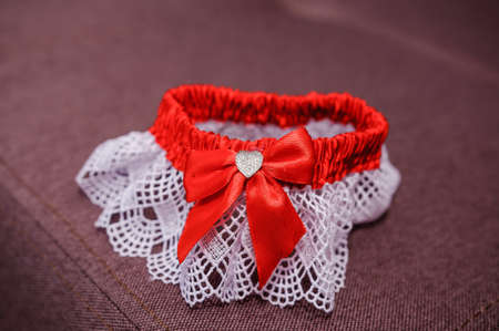 Red bride garter on brown background