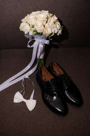 White bow tie, black classic shoes and bridal bouquet with white roses on a brown background