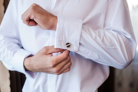 The man fastens the cufflink on the sleeve of his shirt. The groom fastens a button on the sleeve of his shirt
