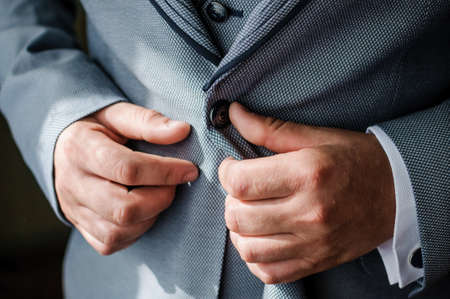 The man fasten a button on his jacket. The groom fasten a button on his jacket Banque d'images