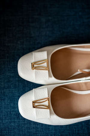 White shoes of the bride on a blue background. Wedding accessories