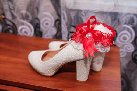 White female shoes and a garter of the bride on a brown background. Wedding accessories for the bride