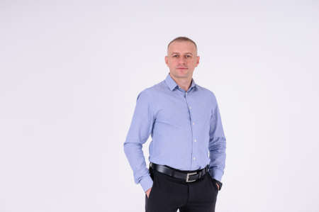 A man in a blue shirt and black trousers stands on a white background