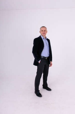 Man in blue shirt, black trousers and blue jacket on white background Standard-Bild