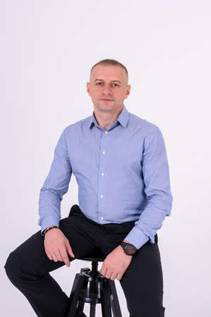 A man in a blue shirt and black trousers sits on a black stool on a white background