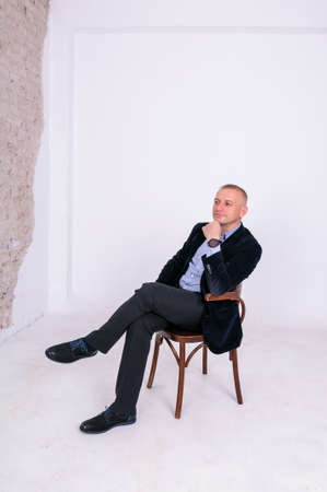 A man in a blue shirt, black trousers and a blue jacket sits on a black stool on a white background