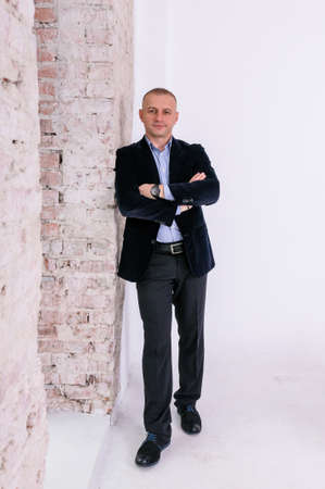 A man in a blue shirt, black trousers and a blue jacket stands against a brick wall background