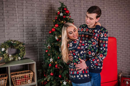 A guy with a girl in a sweater and jeans are hugging on the background of a Christmas tree and red gifts