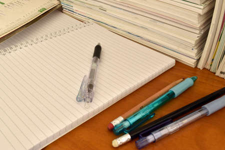 evening newspaper: Stack of books notebook with pen and pencil Stock Photo
