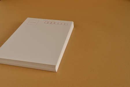 batch: Batch of blank postcards on orange table