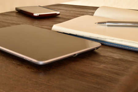 blank tablet: business workplace with tablet, smartphone with blank skrin and empty notebook on wooden table Stock Photo