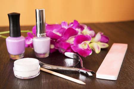 Strumenti del manicure su un tavolo di legno con l'orchidea