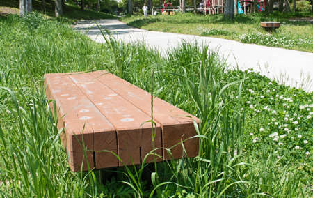 stumped: Bench on green grass field backgrounds in park Stock Photo