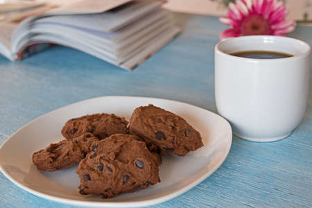 choco chips: chocolate chip cookies on white plate wih cup of coffe on blue background Stock Photo
