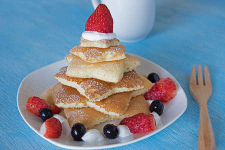 pancake week: pancakes christmas tree with strawberry and blueberry in blue wooden blackground