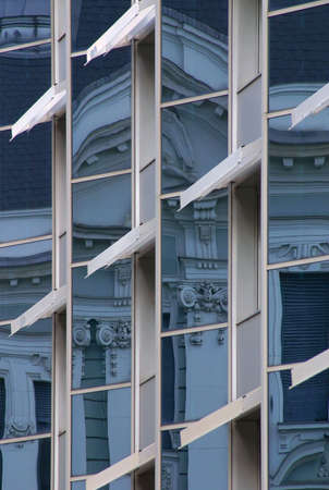 The old building is reflected in the window of the modern building. Stock Photo