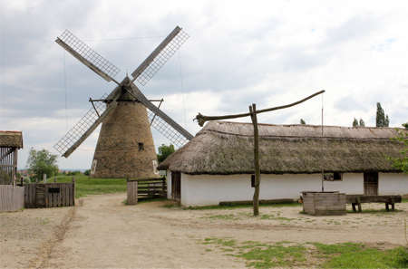 Rural farm in the background with a windmill. Stock Photo
