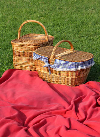 Picnic baskets and blankets in the grass. Stock Photo