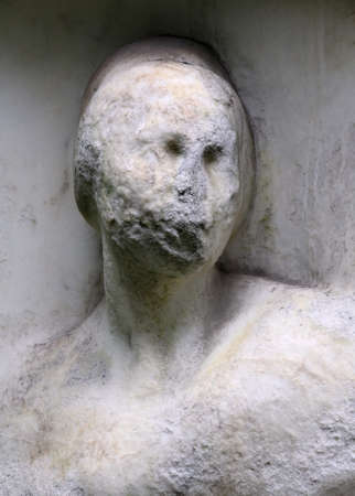 Eroded stone sculpture memorial grave at the cemetery  Stock Photo