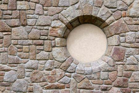 Round window on a stone wall Stock Photo