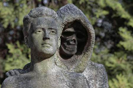 Death skeleton statue symbol tombstone in the cemetery. Stock Photo