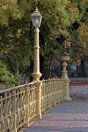 balustrades: Yellow street lamp on the bridge railing.