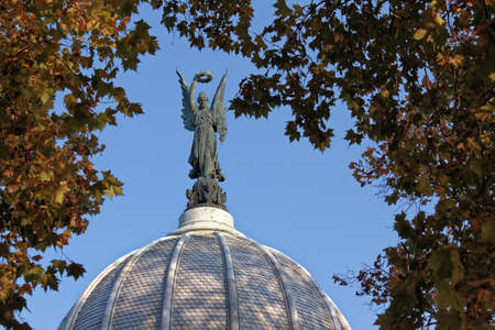 Dome angel statue at the peak foliage framed.