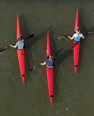Three female kayakers on the water from above.