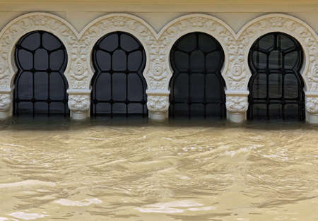 The flood reaches up to arched carved windows.