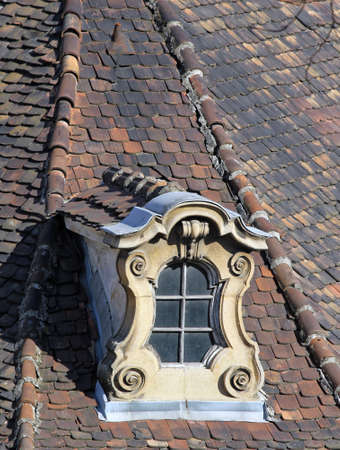 weathered old ornate dormer windows and roof tiles.