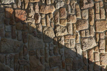 Dry stone wall texture background, in searing light and diagonal shadow.