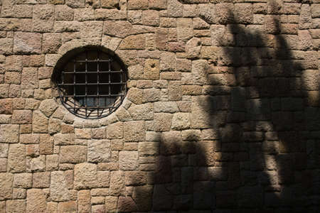 Stone wall with circular church window with wooden shadow.